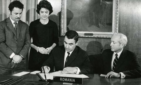 Washington,15 decembrie 1975. Florea Dumitrescu semnează acordul de aderare a României la FMI şi BIRD. În picioare, diplomatul Mircea Răceanu, aflat la post în SUA, şi soţia lui